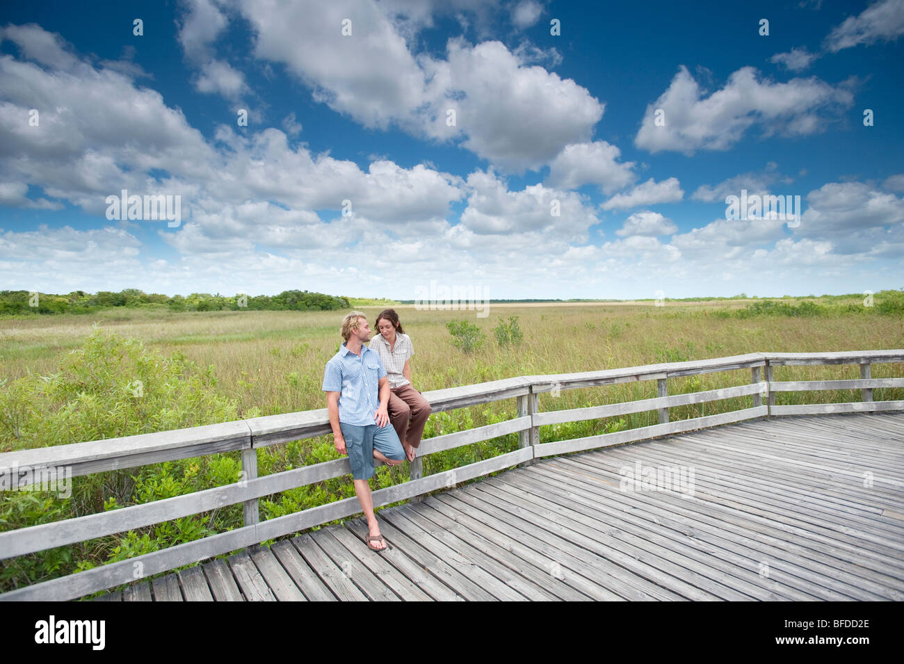 A couple pauses during a hike to lean against a wooden railing in Everglades National Park, Florida. - Stock Image