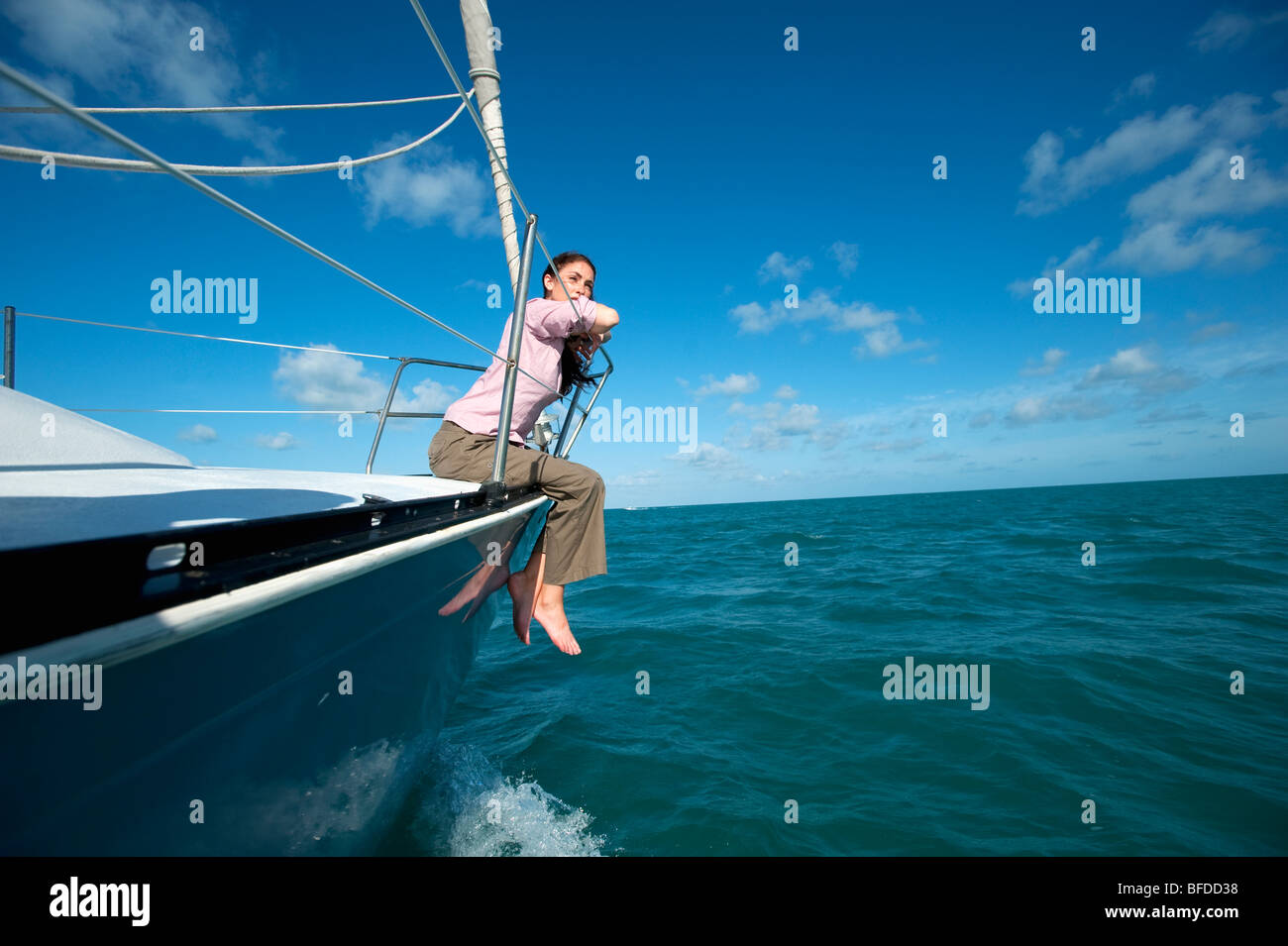 A woman sits on the bow of a boat off of Florida. - Stock Image