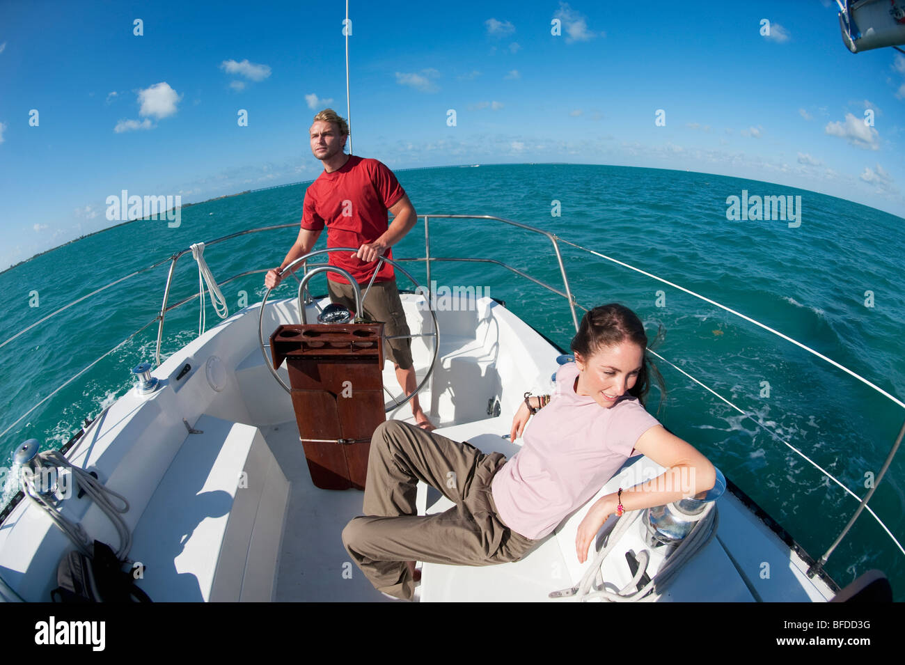 A man pilots a boat off of Florida while a woman sits nearby. - Stock Image