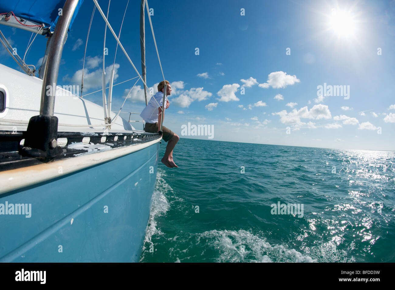 A man sits on the bow of a boat off of Florida. - Stock Image