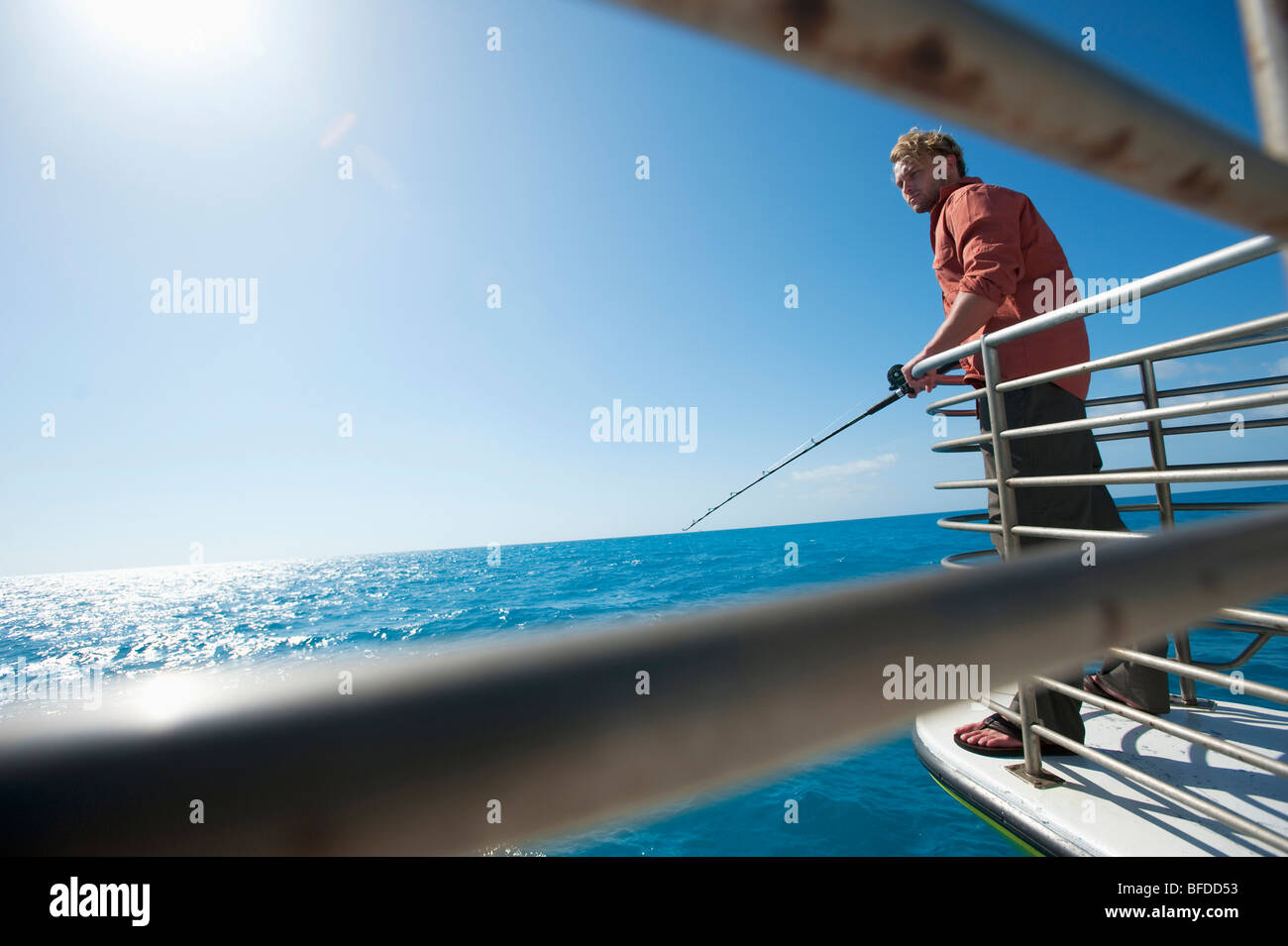 A man fishes off of a boat in Florida. - Stock Image