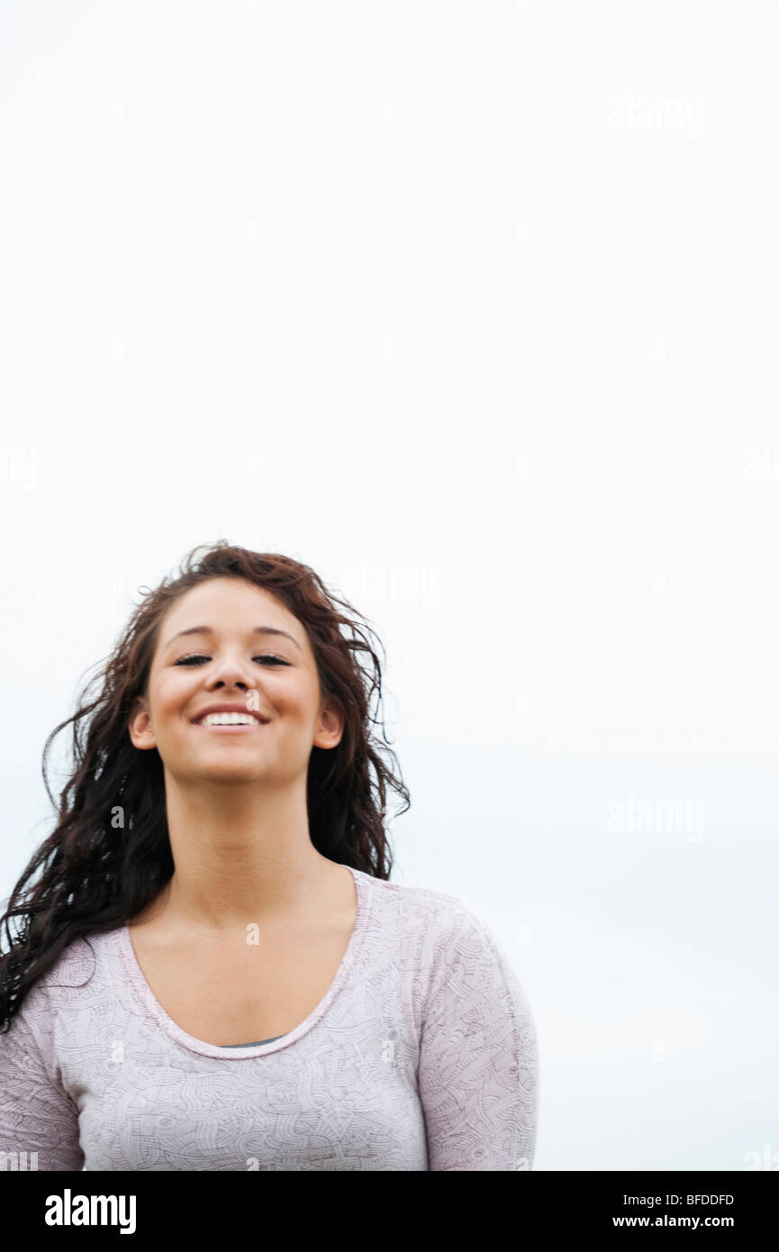 Young woman with dark hair smiles at the camera as her hair blows. - Stock Image