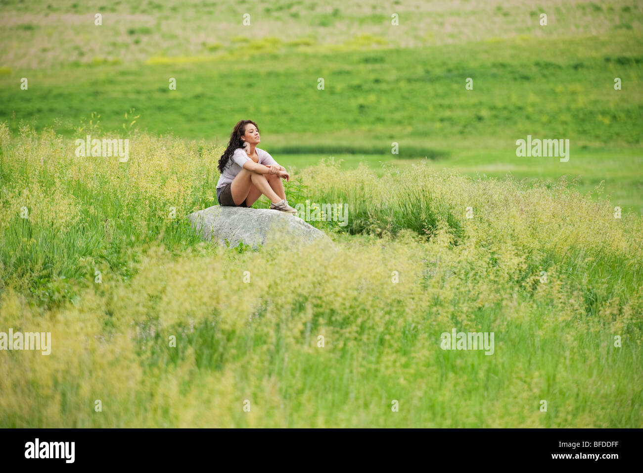 Young woman siting on rock in a bright green field at Spirit Mound, South Dakota. - Stock Image