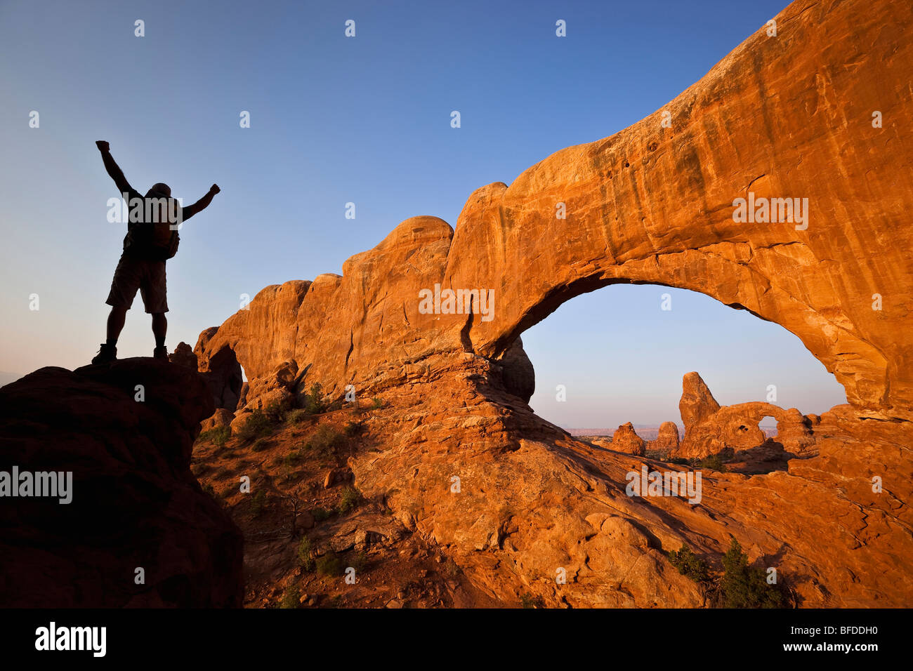 A silhouetted hiker raises his arms beside an arch in Arches National Park, Utah. - Stock Image