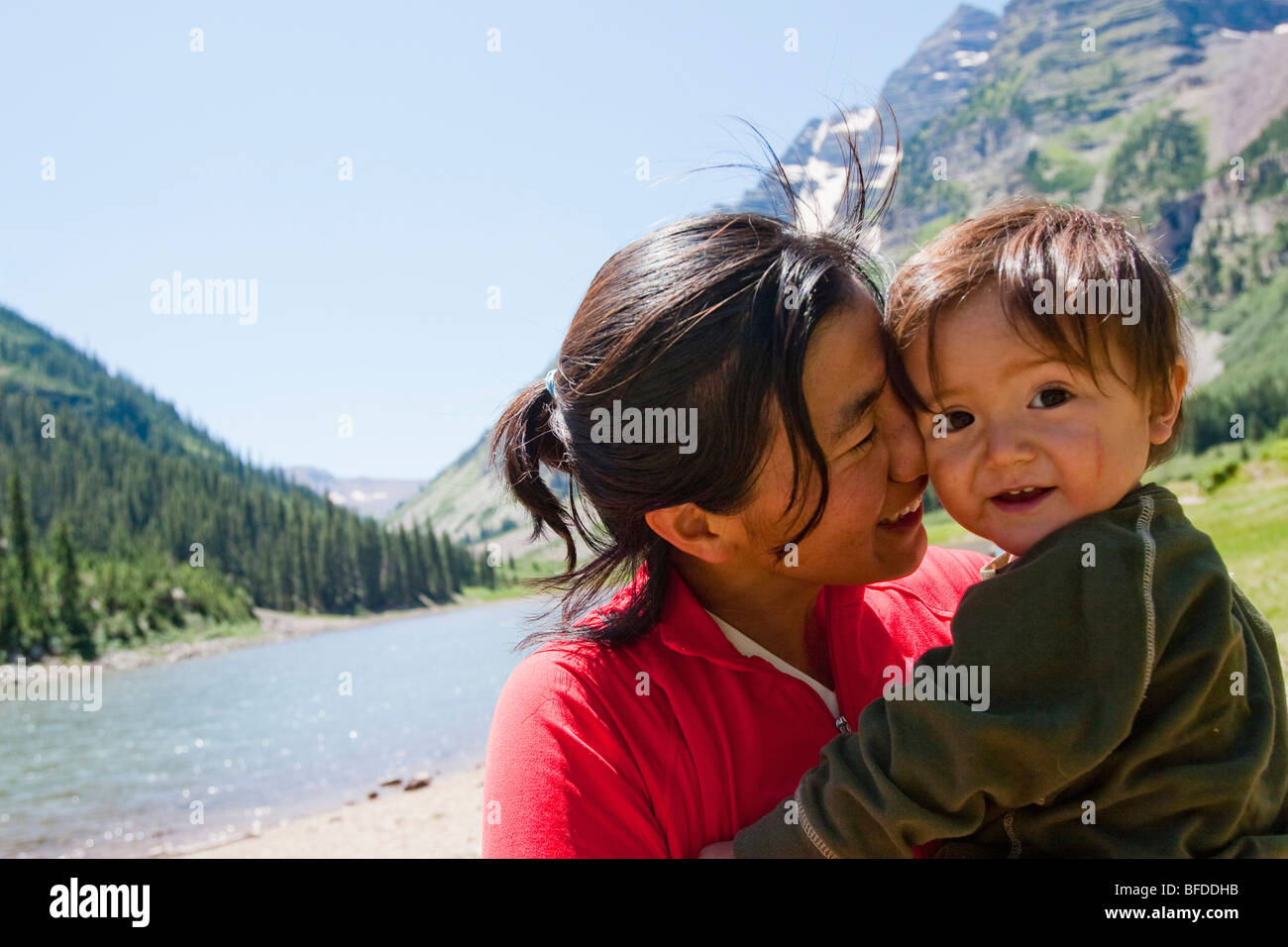 A mother and her child at Crater Lake in the Maroon Bells in Snowmass Wilderness on a multi-day backpacking trip. - Stock Image