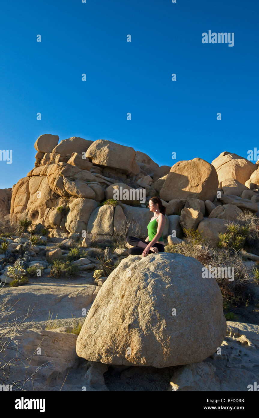 A young woman practices yoga on a rock outdoors in California. - Stock Image