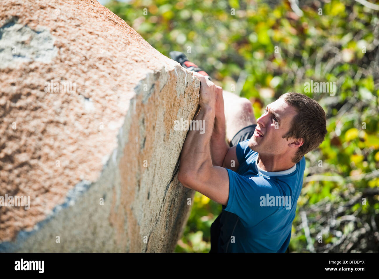 A climber traverses with his hands and a high heel hook on a granite boulder. - Stock Image
