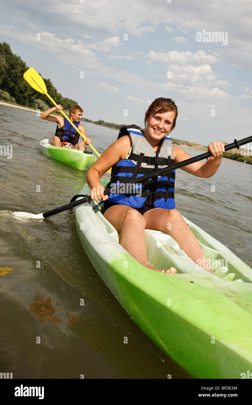 Young teenage girl smiles paddling kayak through waters of Yellowstone River Eastern Montana. Teenage boy paddles - Stock Image