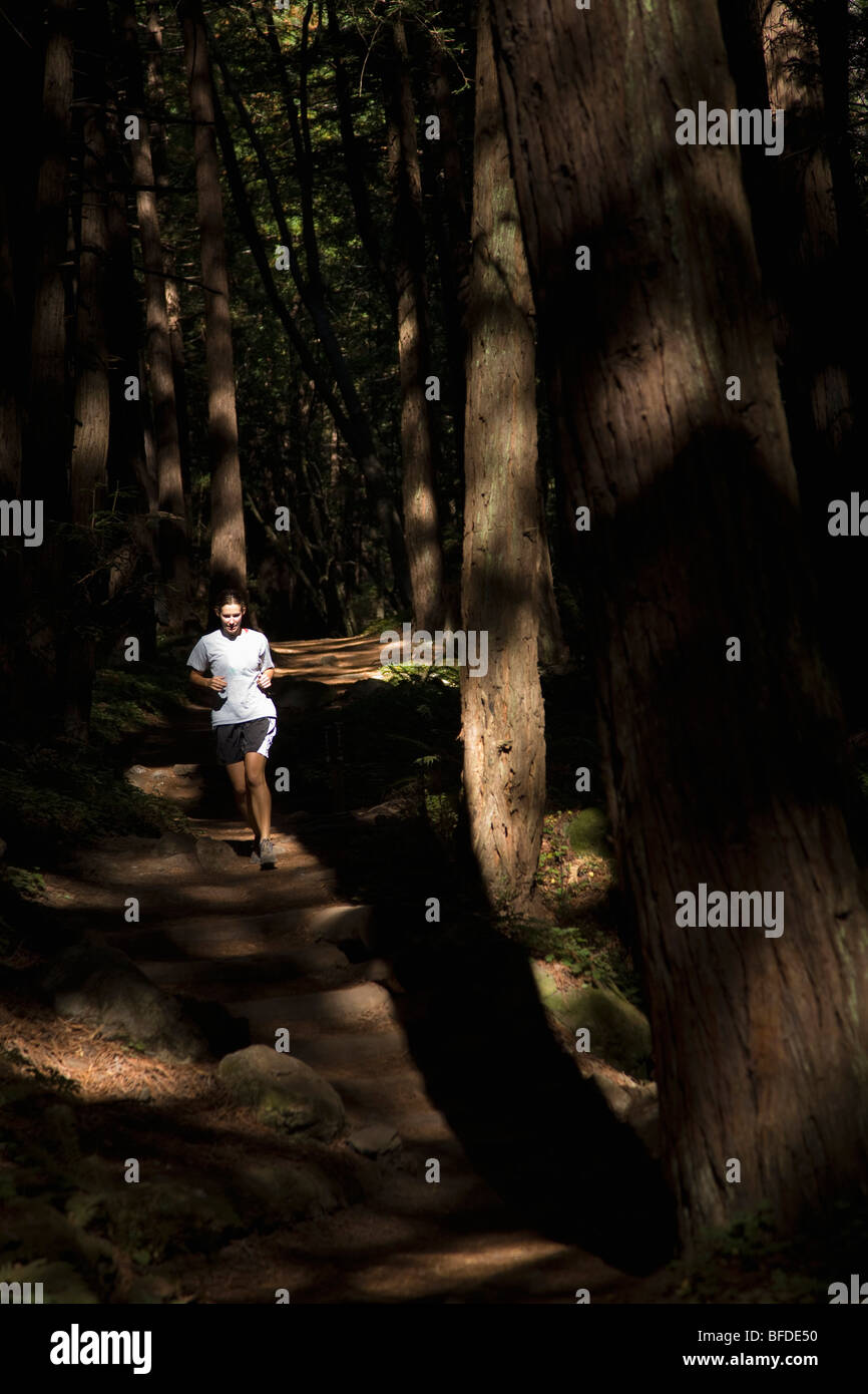 A women running a waterfall trail in Big Sur, California. - Stock Image