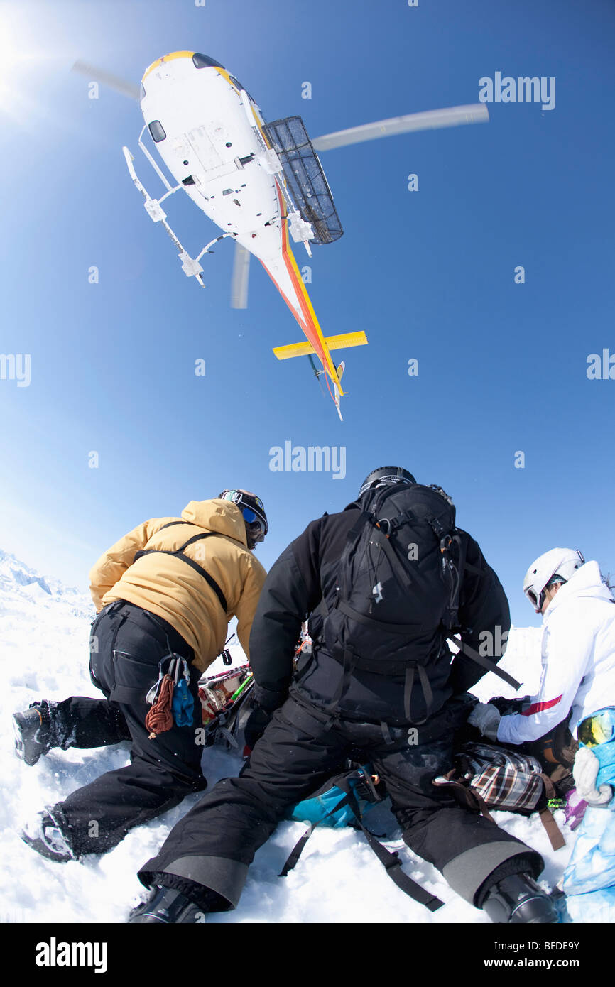 Three skiers with skis and backpacks shield themselves from the blast of a helicopter taking off in Valdez, Alaska. - Stock Image