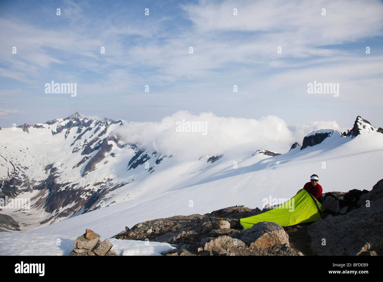 A young man sets up his bivy sac on a rock outcrop on a glacier while climbing a jagged mountain. - Stock Image