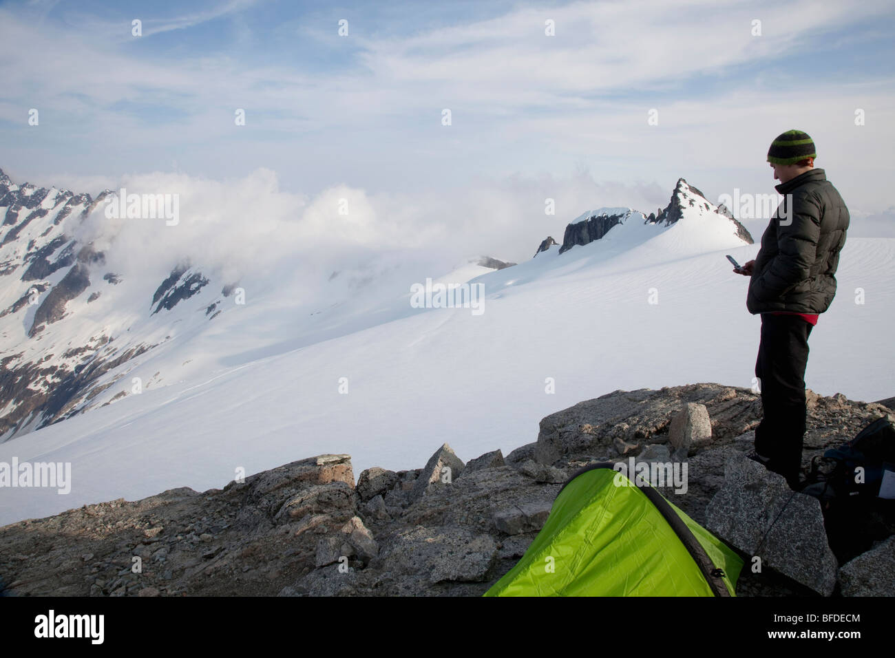 Young climber checks his cell phone for coverage while standing on a rock outcrop on a glacier with jagged peaks - Stock Image