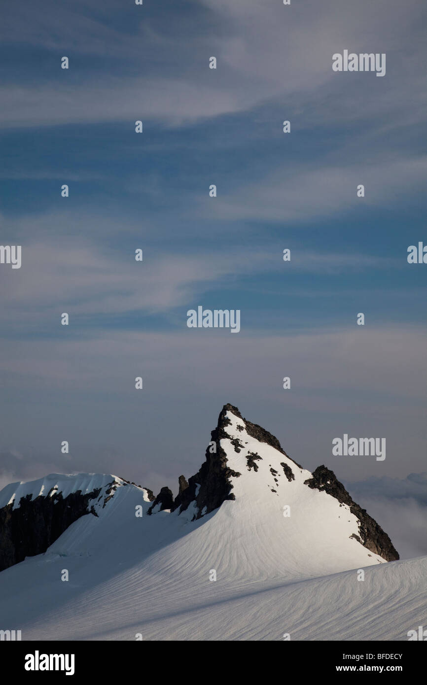 A snowy, jagged peak with a blue sky above. - Stock Image