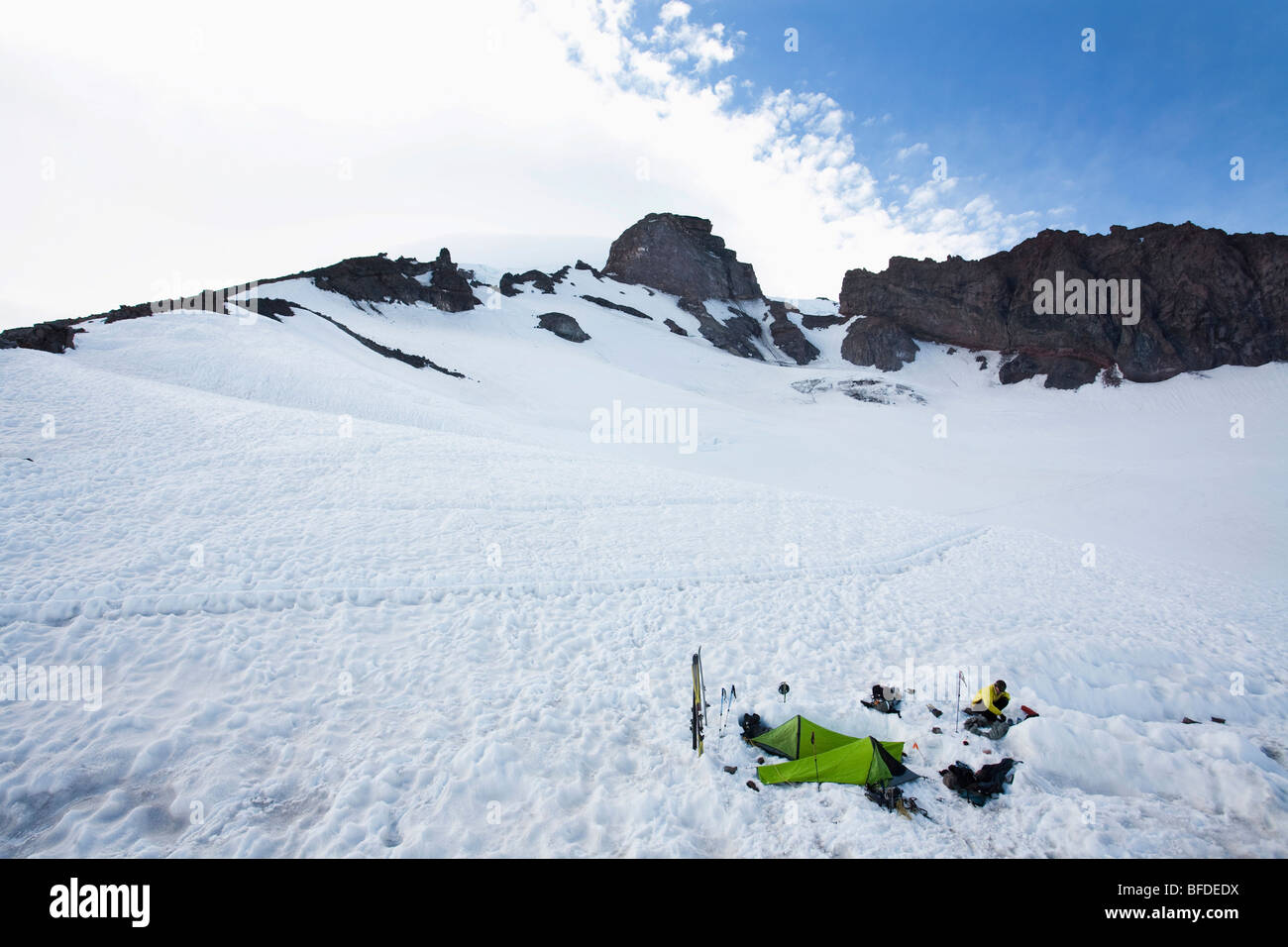 A climber melts snow near his campsite where two bivy sacks are set up. Stock Photo