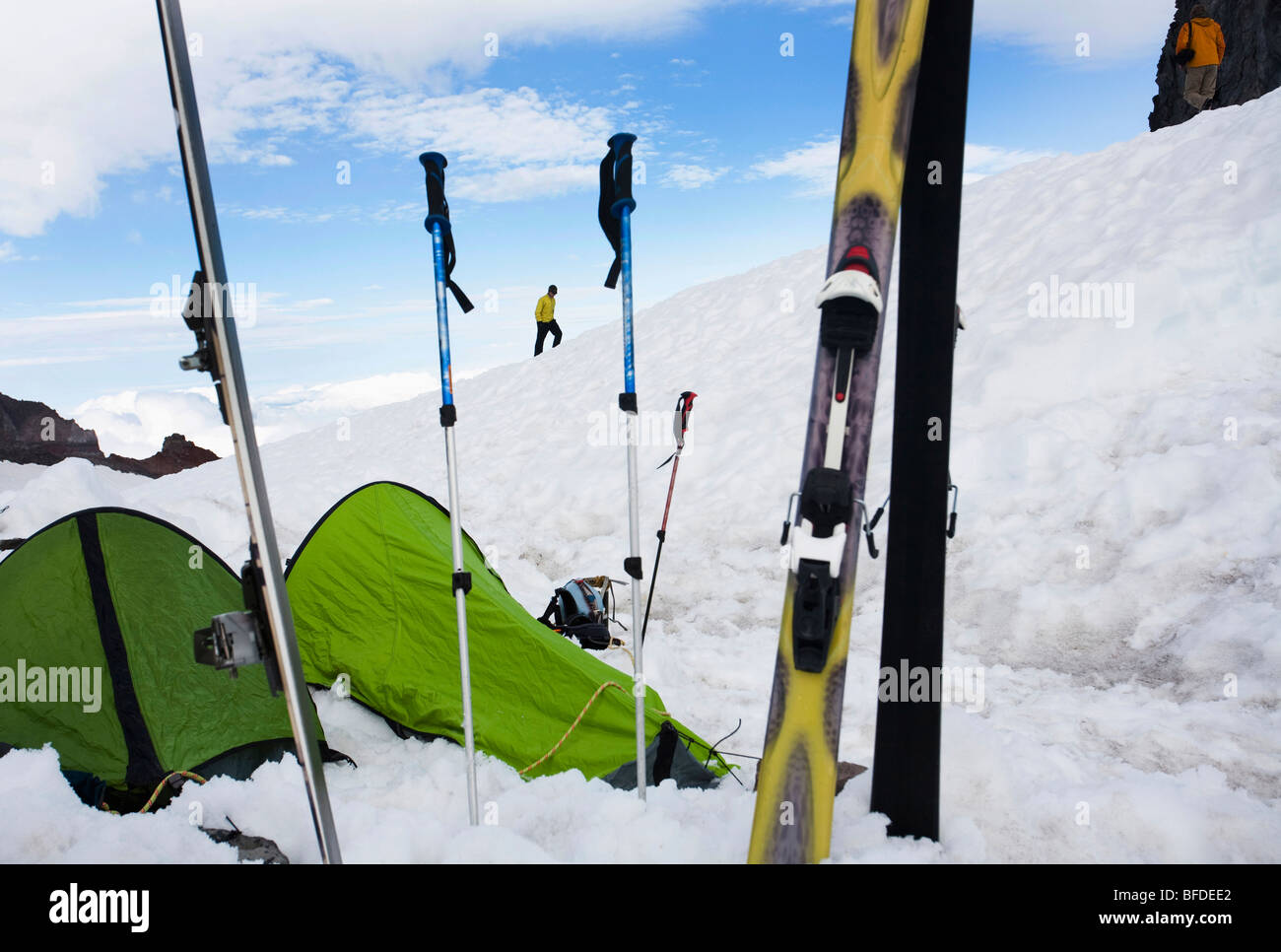 A climber walks the ridgeline with two bivy sacks and skis in the foreground. - Stock Image