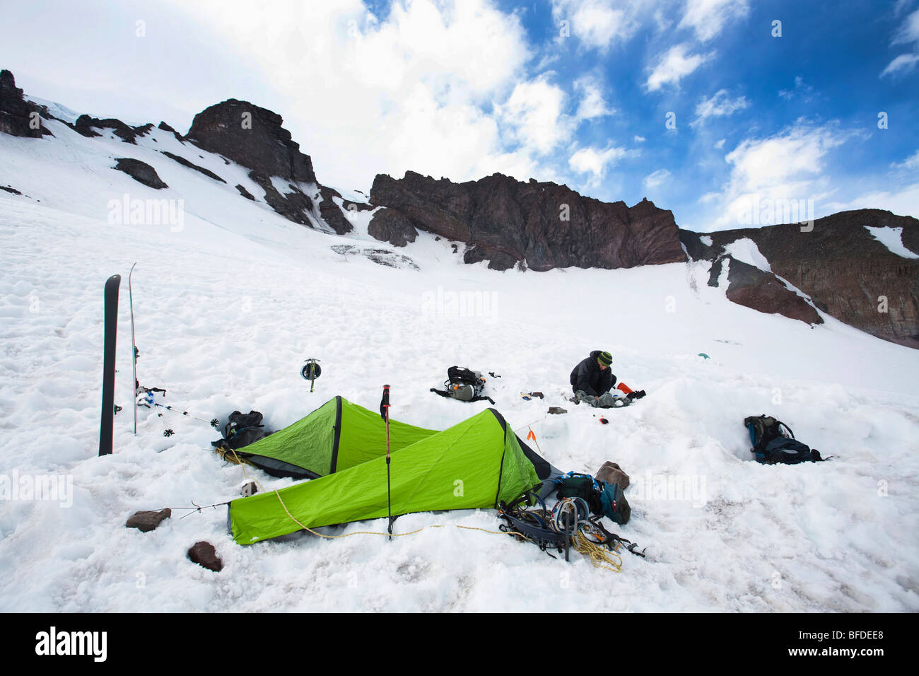 Two bivy sacks and skis indicate a campsite in the middle of snowfield.eld. - Stock Image