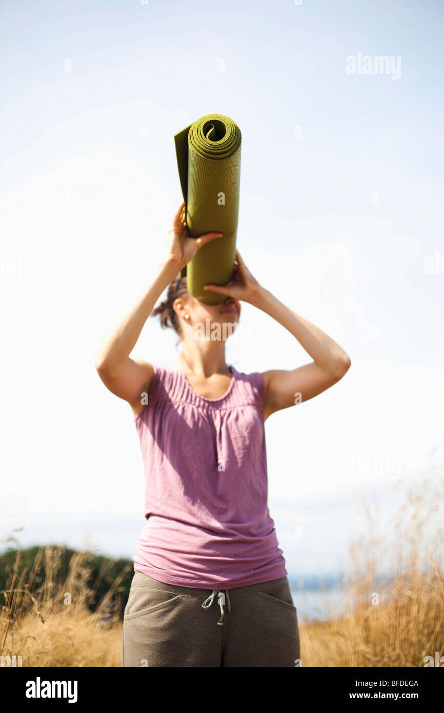 A young woman playfully looks through her yoga mat, acting like it is a telescope. - Stock Image