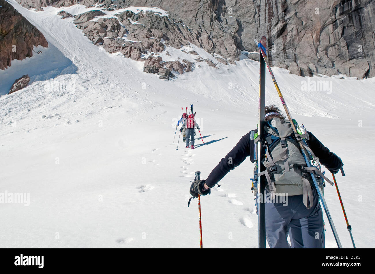 Three backcountry skiers approach a couloir in the spring in Rocky Mountain National Park, Colorado. - Stock Image