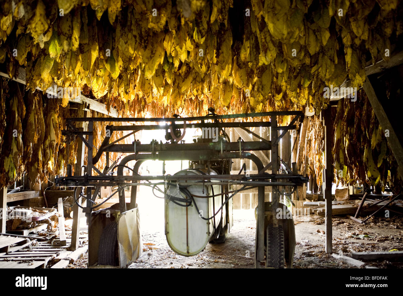 Farm machinery in a tobacco barn. - Stock Image