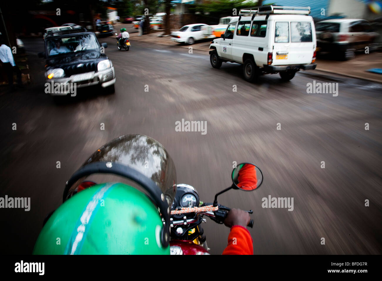 A view from the backseat of a moving motorcycle through the streets of Kigali, Rwanda. - Stock Image