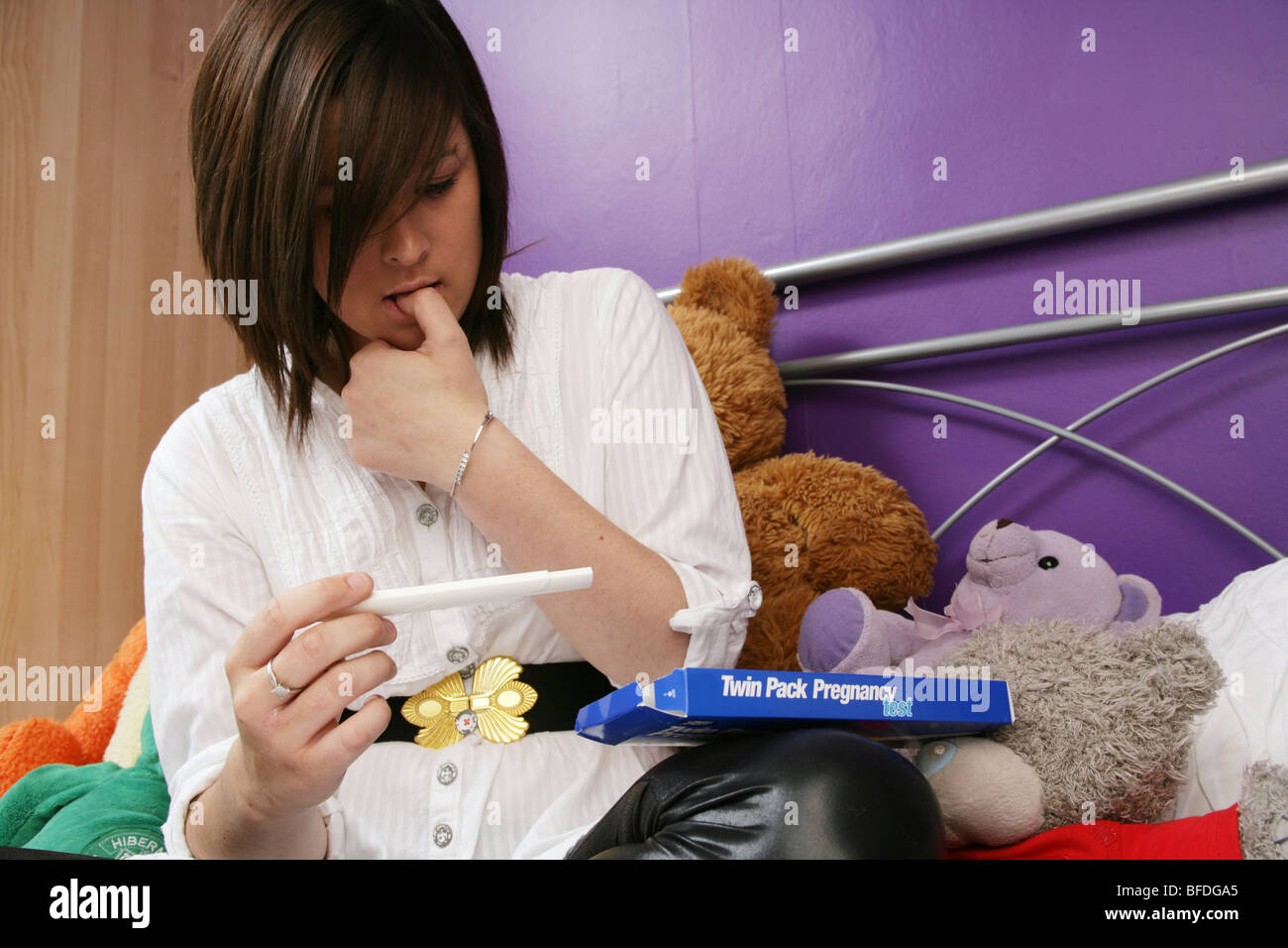 Young woman sitting on her bed checking a pregnancy tester - Stock Image