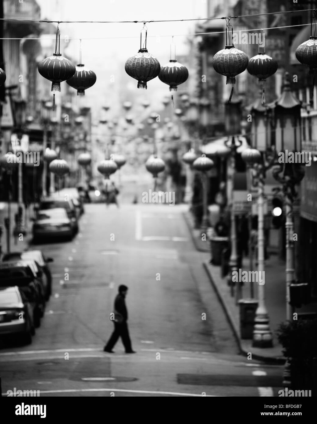 A person walking across  Grant Avenue in the early morning in Chinatown, San Francisco, California. - Stock Image