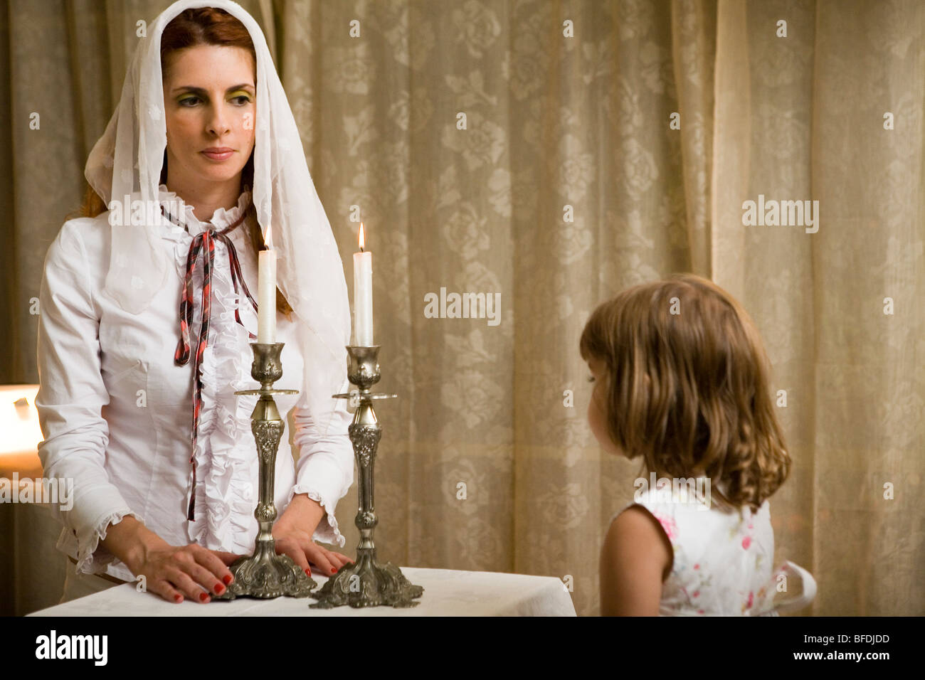 Mother And Daughter Lighting Shabbat Candles.   Stock Image