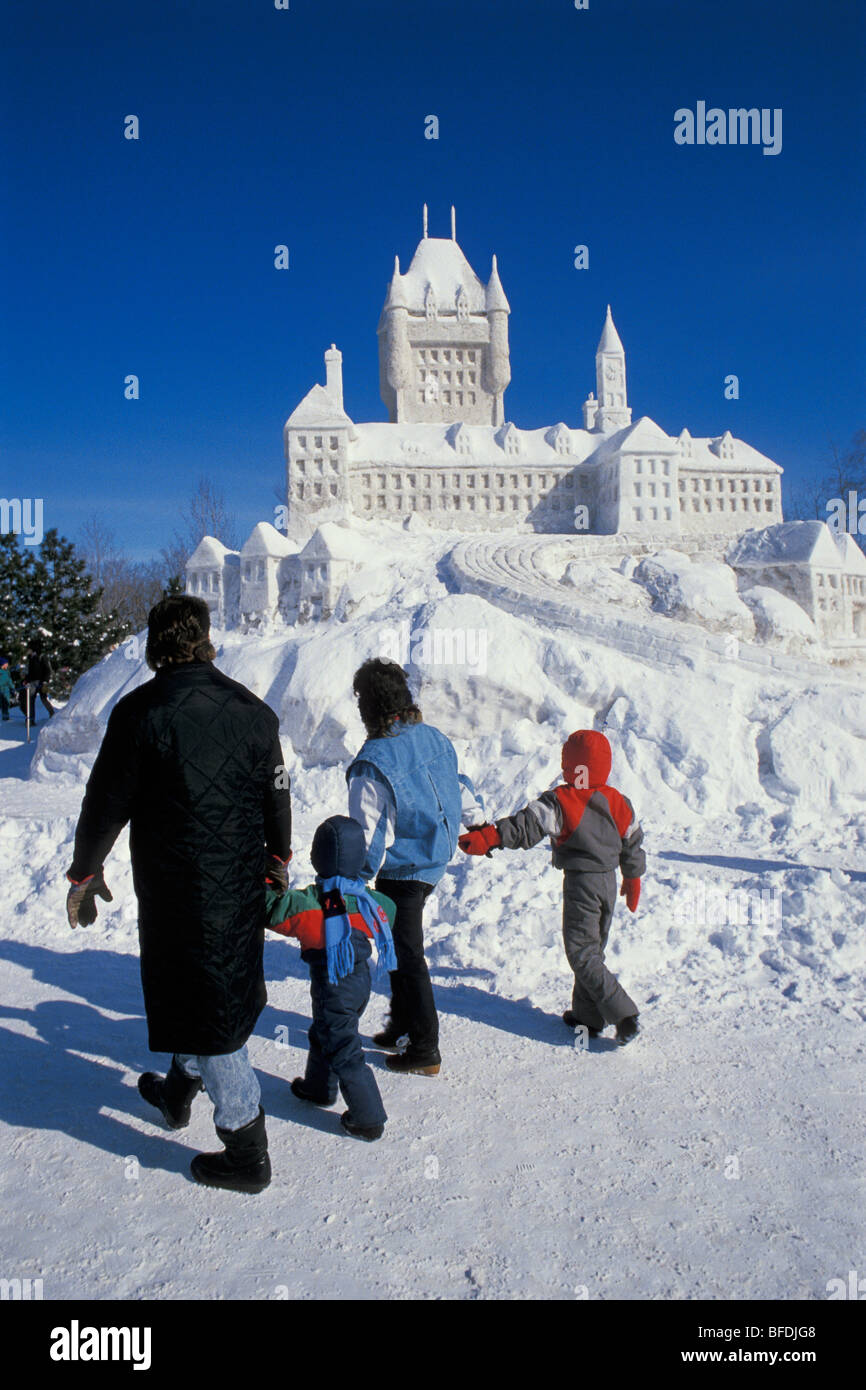 Family walking by snow sculpture at Winterlude Festival, Jacques Cartier Park, Hull (Gatineau), Quebec, Canada. - Stock Image