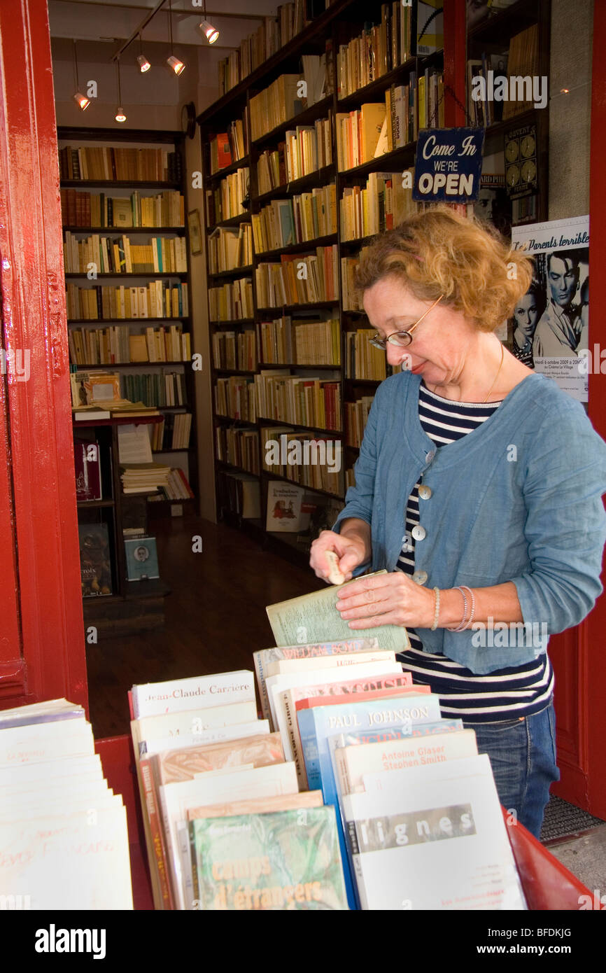 Bookseller cleaning a second-hand book in Paris, France. - Stock Image