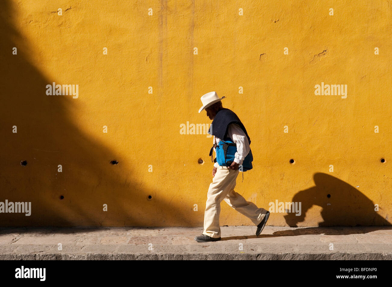 Man walking in front of yellow wall; San Miguel de Allende, Mexico. - Stock Image