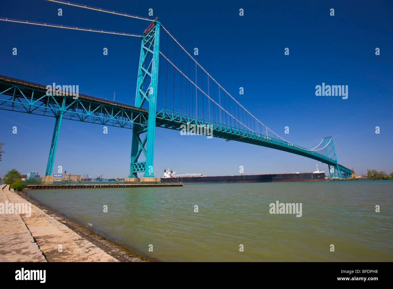 Large bulk carrier ship passing beneath the Ambassador Bridge  Windsor, Ontario, Canada and Detroit, Michigan, USA - Stock Image