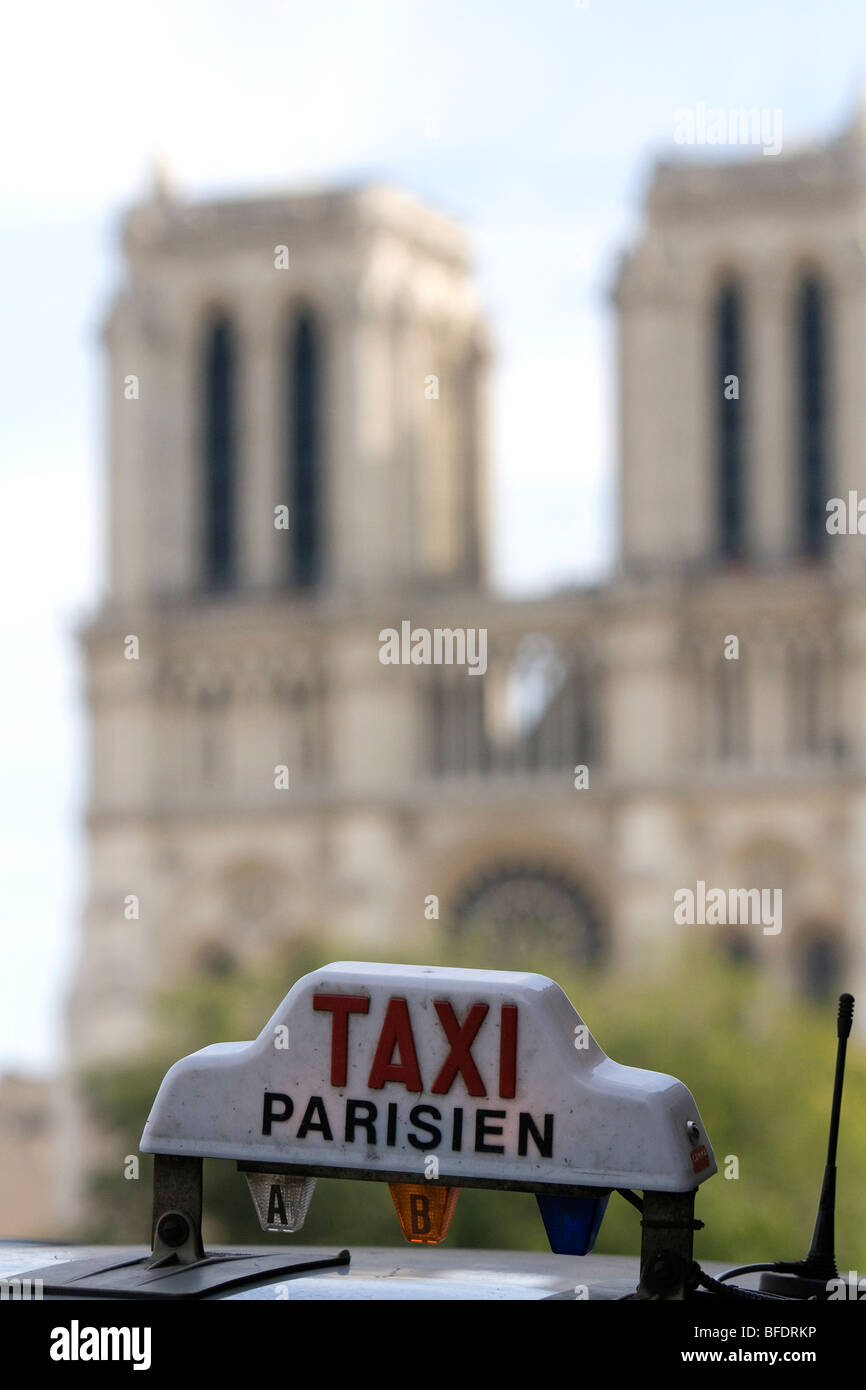 Sign atop a taxicab in front of the Notre Dame de Paris, France. - Stock Image