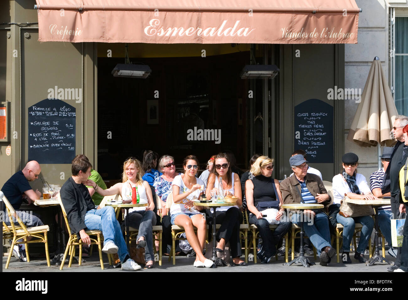 People dine outdoors at a sidewalk cafe in Paris, France. - Stock Image