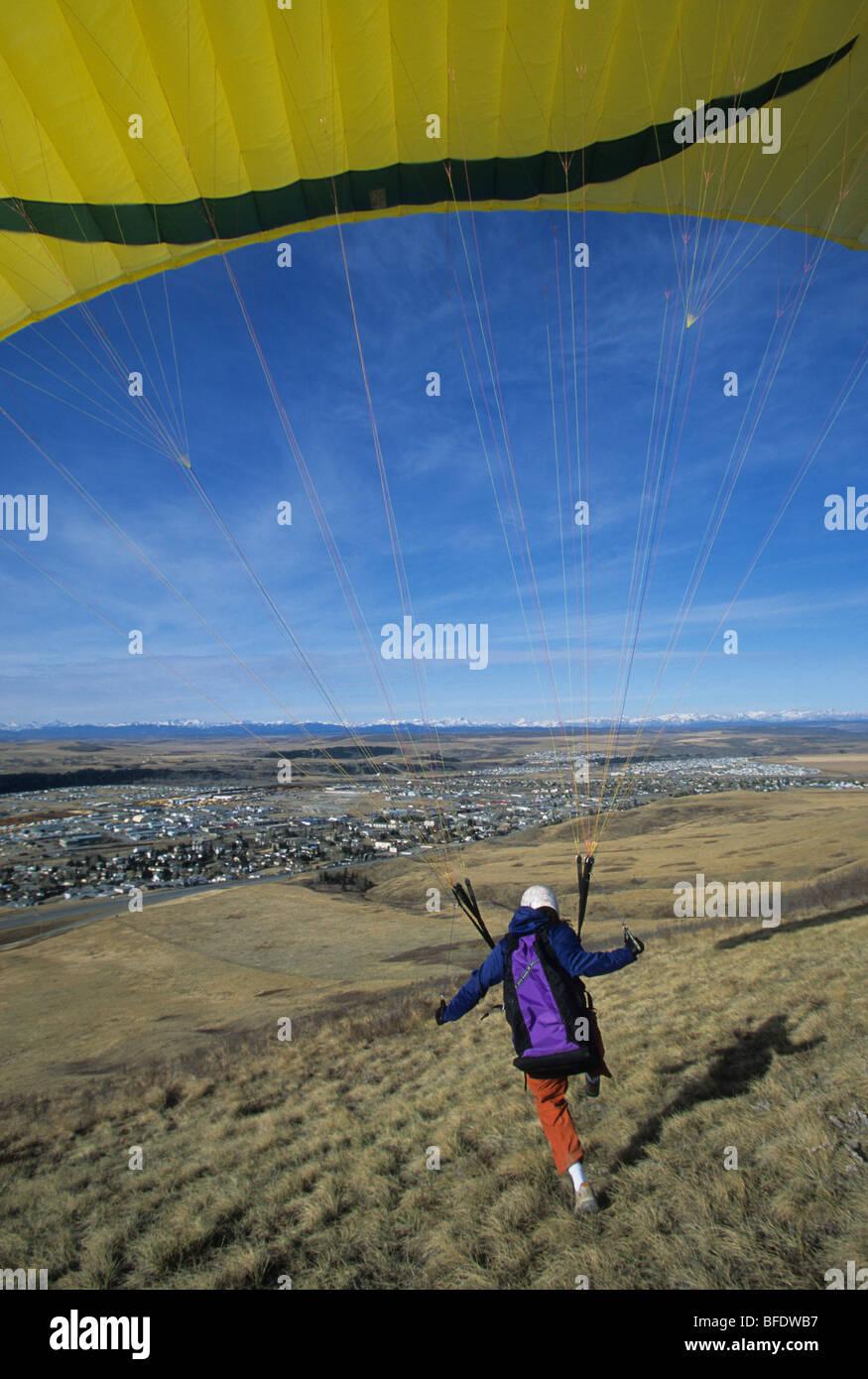 A paraglider landing on a grassy field in Cochrane, Alberta, Canada Stock Photo
