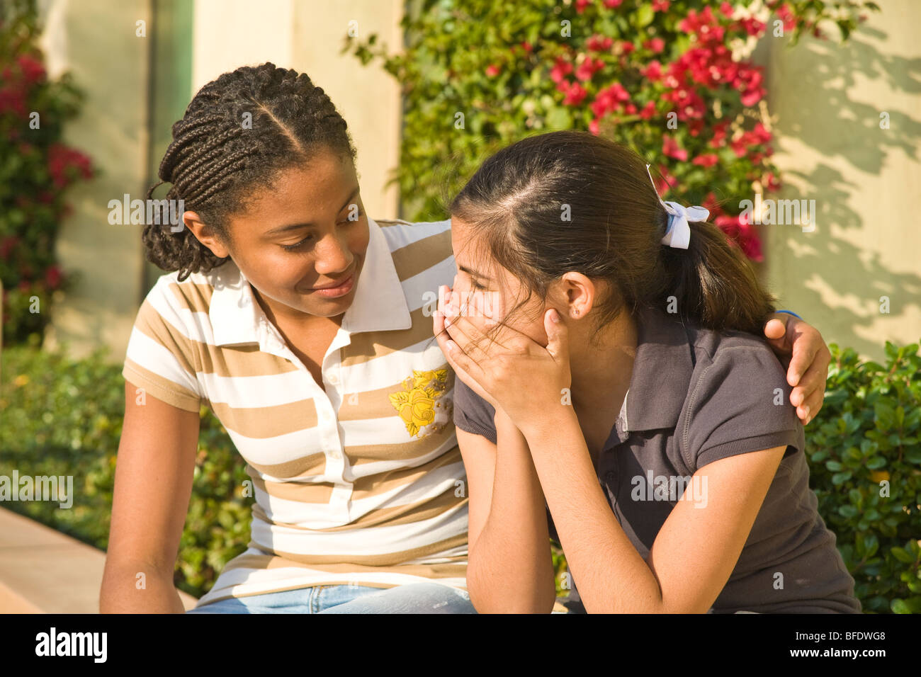 Hang hanging out African American 13-15 year old kind kindly listens listening teenage girl comforts sad girlfriend. - Stock Image