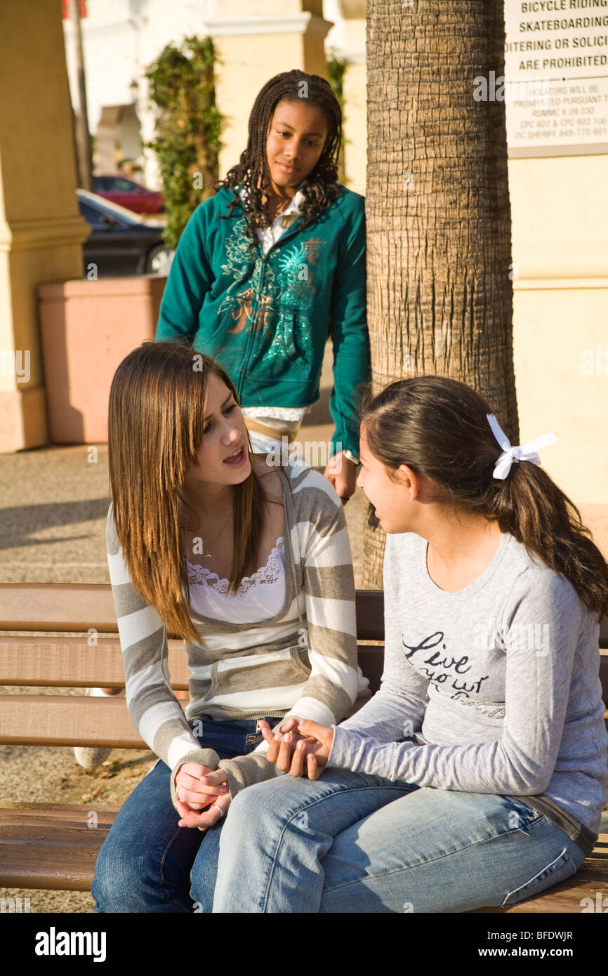 Hang hanging out Diverse group 13-15 year years old  teenage girls talking one sad girl with hurt feelings feels - Stock Image