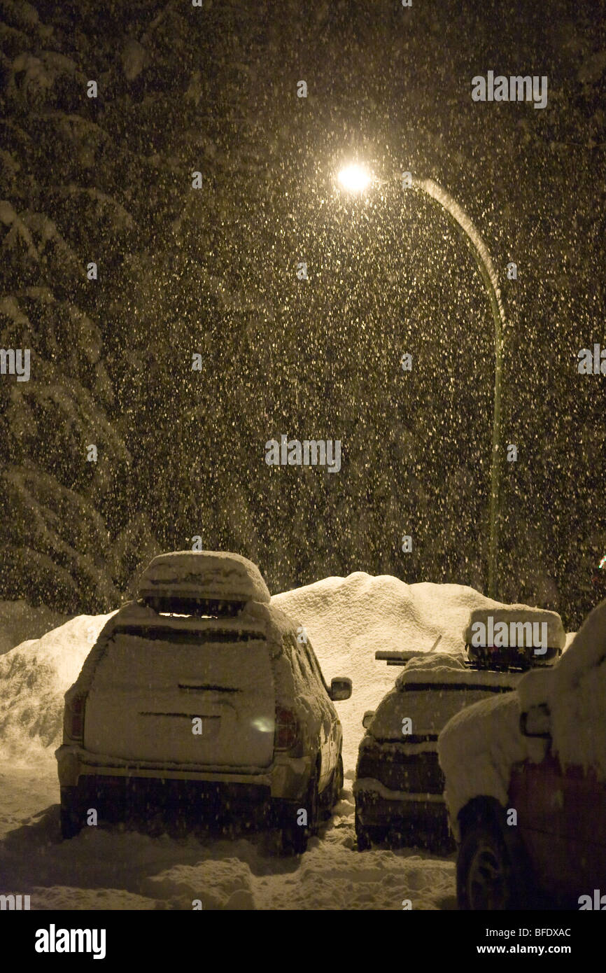 A nighttime winter snowfall in a parking lot in Revelstoke, British Columbia, Canada - Stock Image
