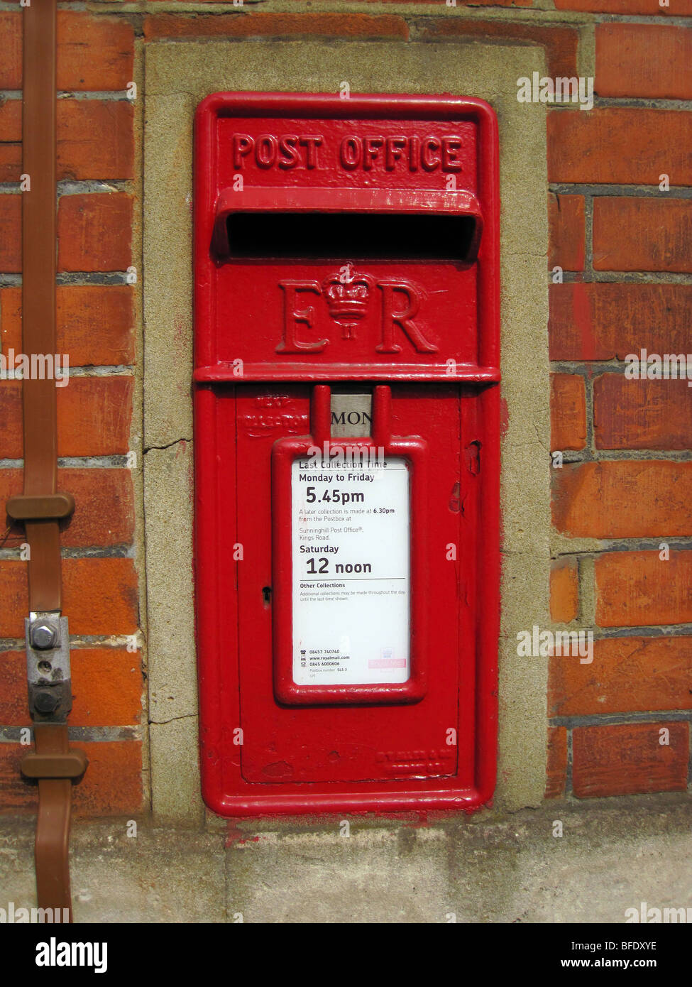 Old fashioned village wall mounted red post or pillar box - Stock Image