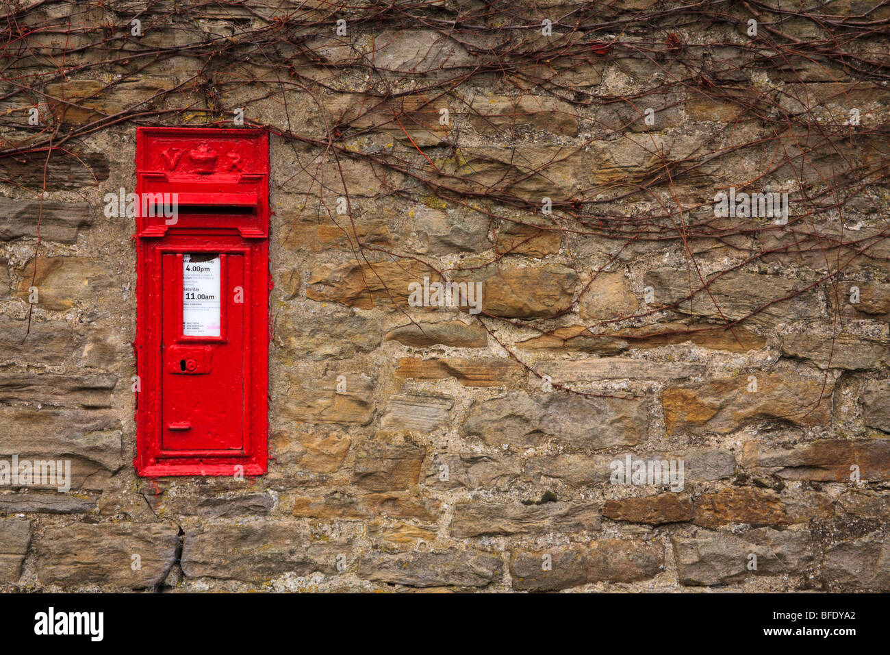 Post box on stone wall of a house in Thwaite, Swaledale Yorkshire Dales, England UK waiting for Christmas mail. - Stock Image