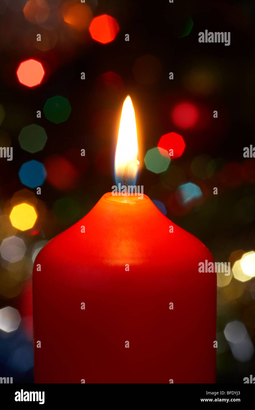 red christmas candle burning alight in front of a christmas tree - Stock Image