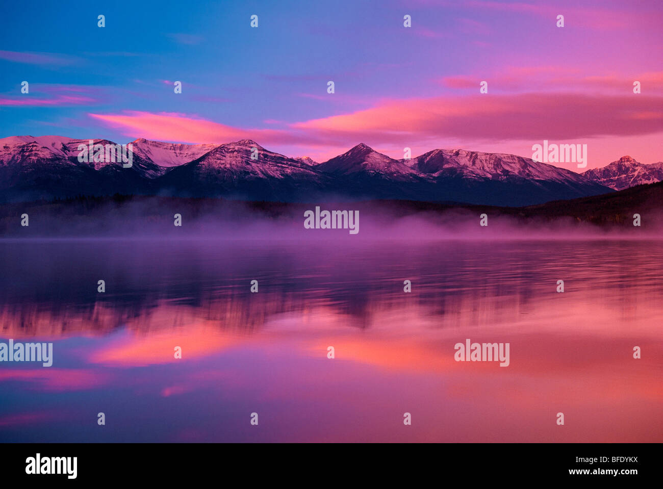 Mountains southwest of Jasper reflected in Pyramid Lake at sunrise, Jasper National Park, Alberta, Canada - Stock Image
