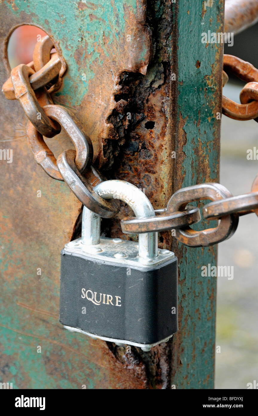 Padlock and rusty chain on old rusted metal gate - Stock Image
