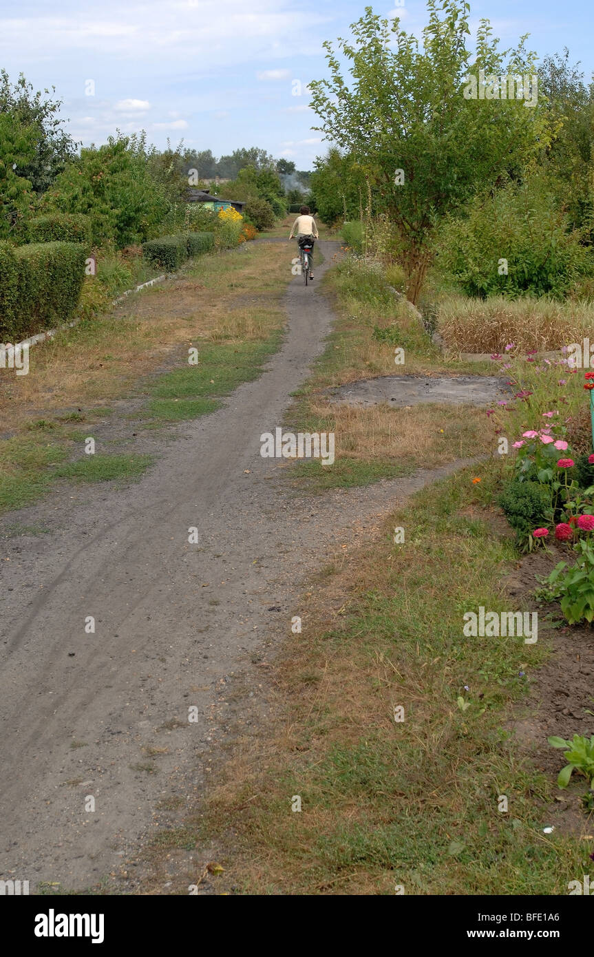 One of a series of photos depicting an older woman riding a bicycle down a dirt trail through a section of individual - Stock Image
