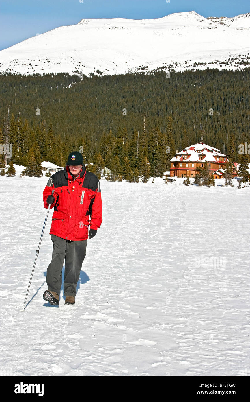 Hiking across frozen Bow Lake near Num Ti Jah Lodge just off the Icefields Parkway in Alberta, Canada. - Stock Image