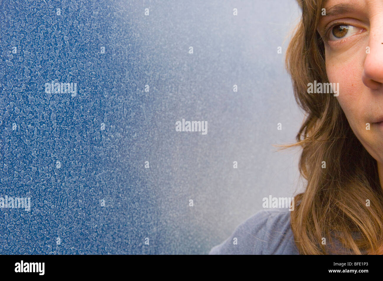 close up of a woman wide awake against a blue wall Stock Photo