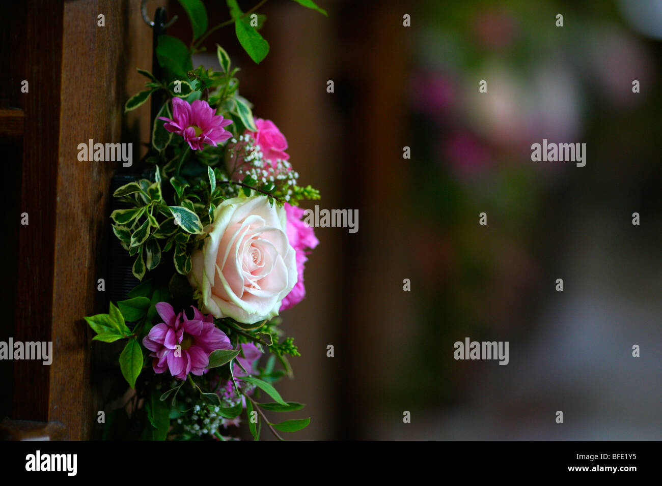 Flowers on the end of a church pew as wedding decoration - Stock Image
