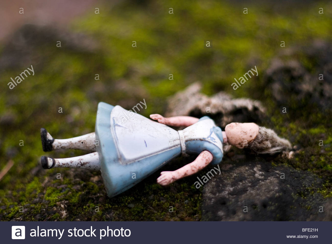A thrown away doll on a rock. - Stock Image