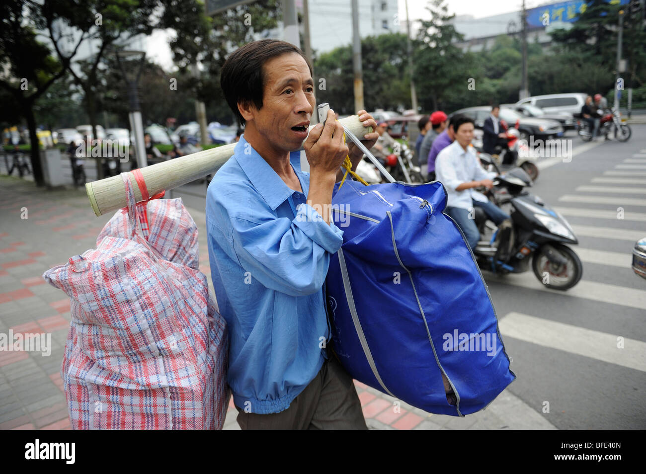 A migrant worker is lost and inquires the way with his mobile phone in Shanghai, China. 16-Oct-2009 - Stock Image
