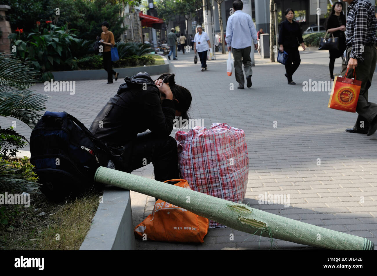 A female migrant worker rests for a while with her luggage in Shanghai, China. 22-ct-2009 Stock Photo