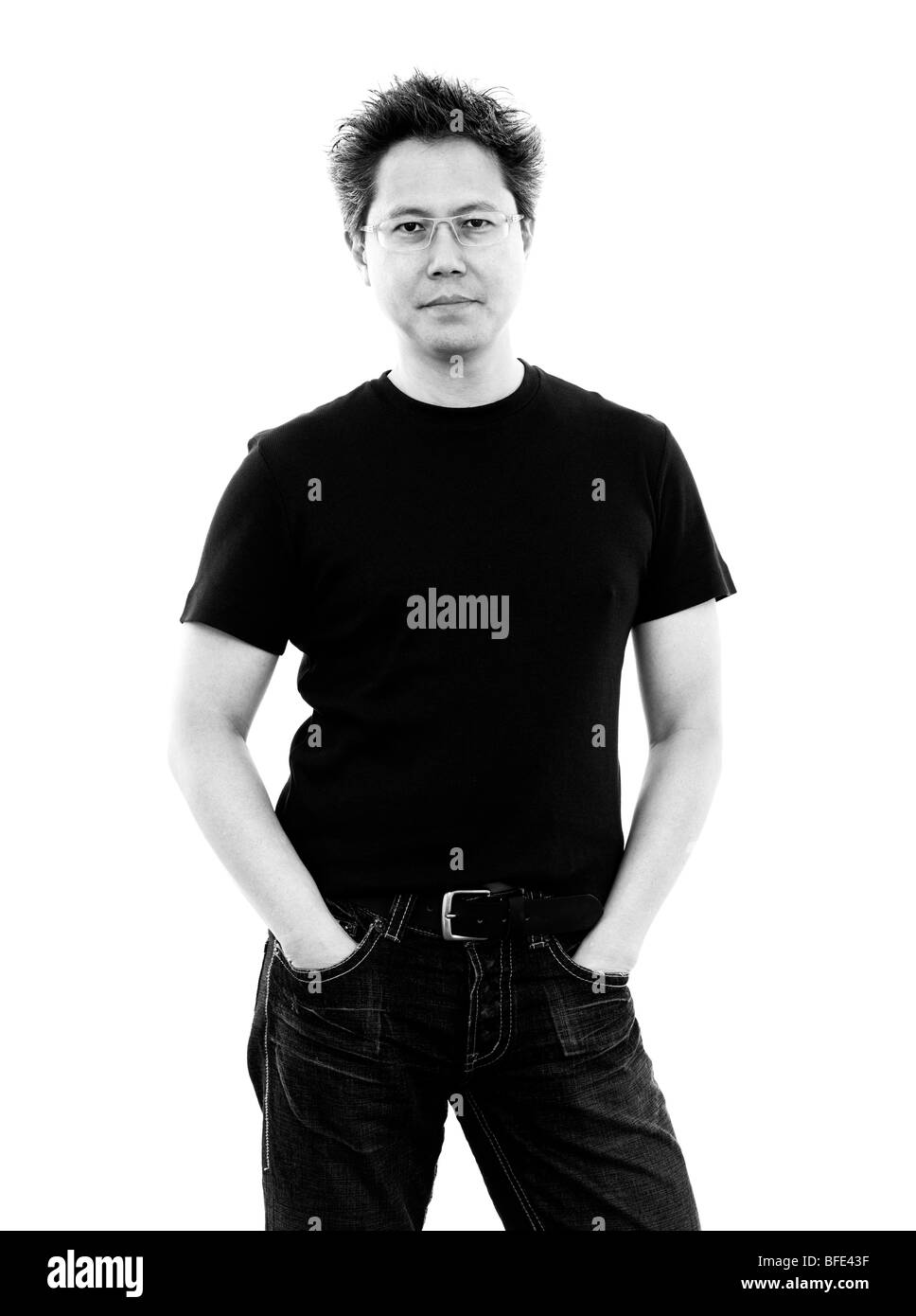 44 year old Asian male wearing jeans and a t-shirt standing against a white background - Stock Image